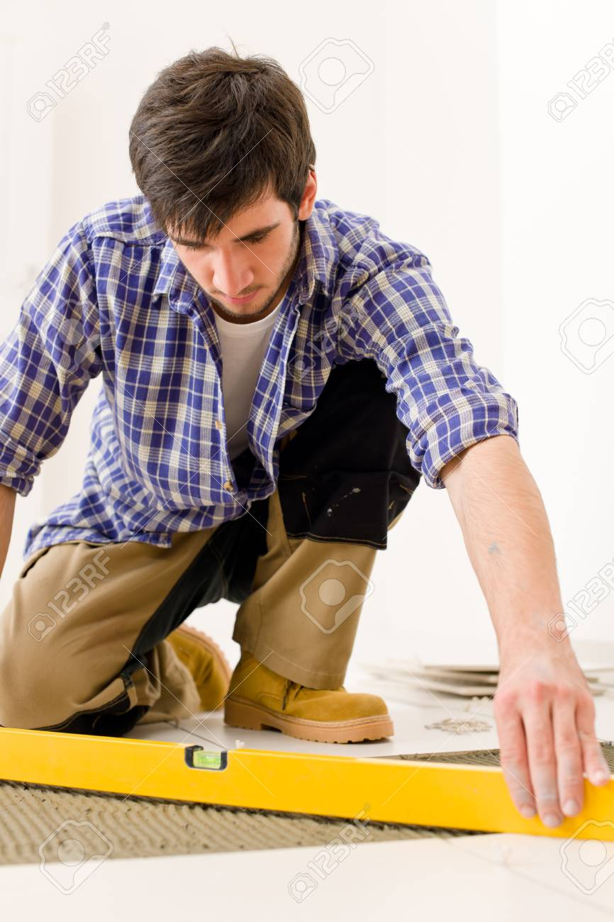 Home tile improvement - handyman with level laying down tile floor Stock Photo - 8417853