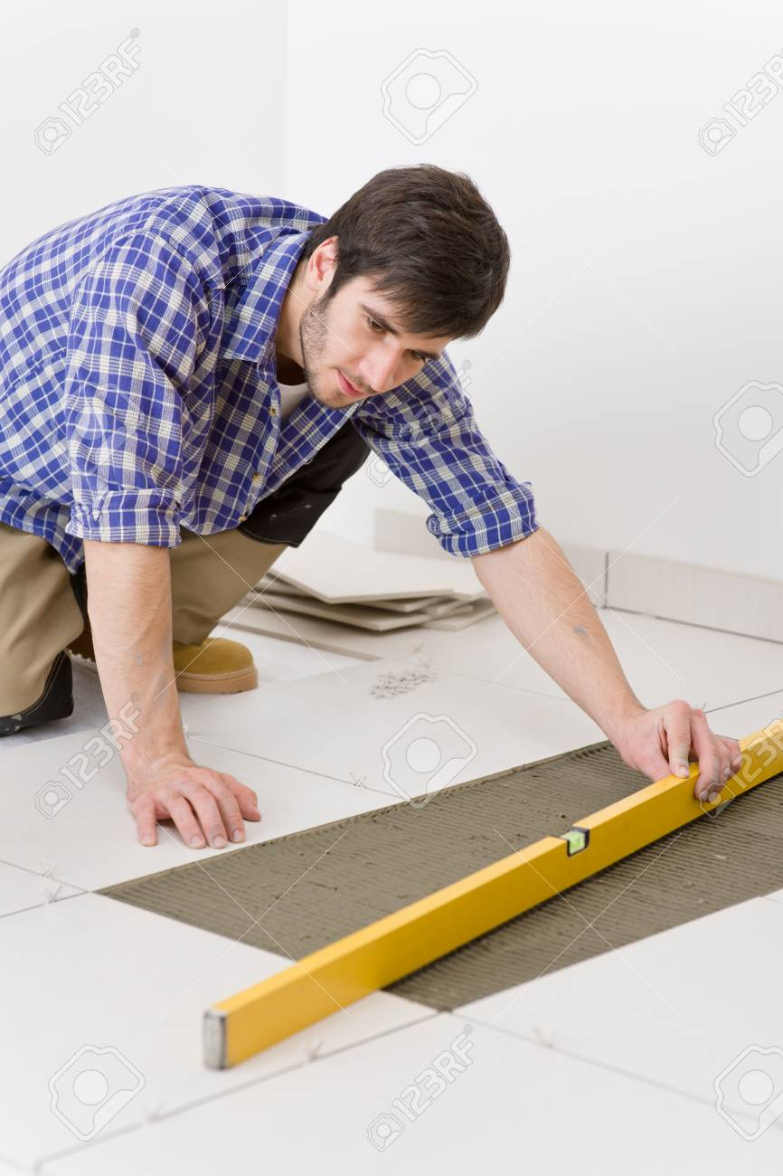 Home tile improvement handyman with level laying down tile stock home tile improvement handyman with level laying down tile floor stock photo 8417851 dailygadgetfo Choice Image