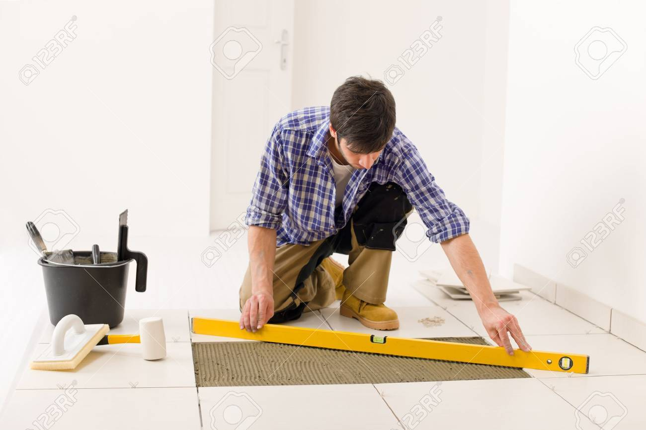 Home tile improvement handyman with level laying down tile stock home tile improvement handyman with level laying down tile floor stock photo 8569191 dailygadgetfo Choice Image