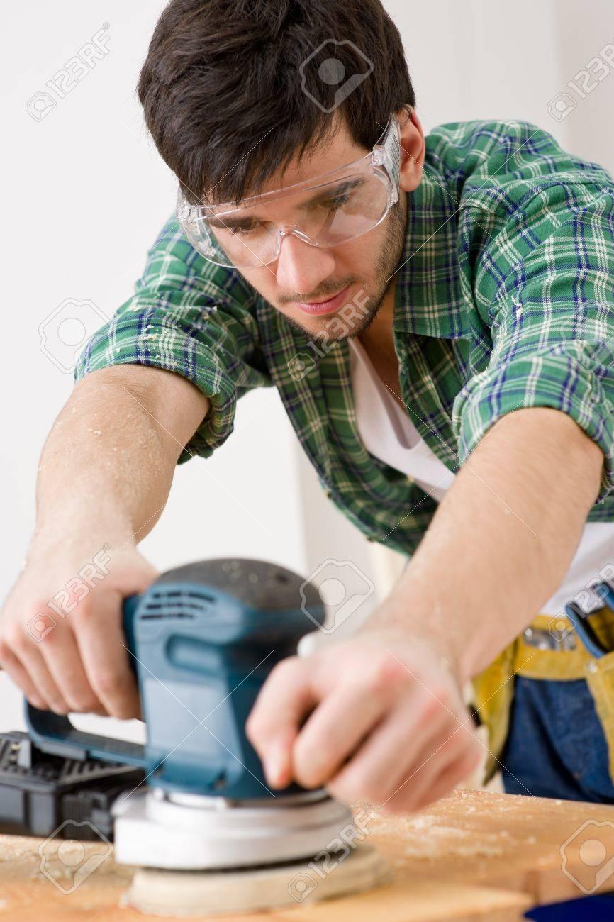 Home improvement - handyman sanding wooden floor in workshop Stock Photo - 8575203
