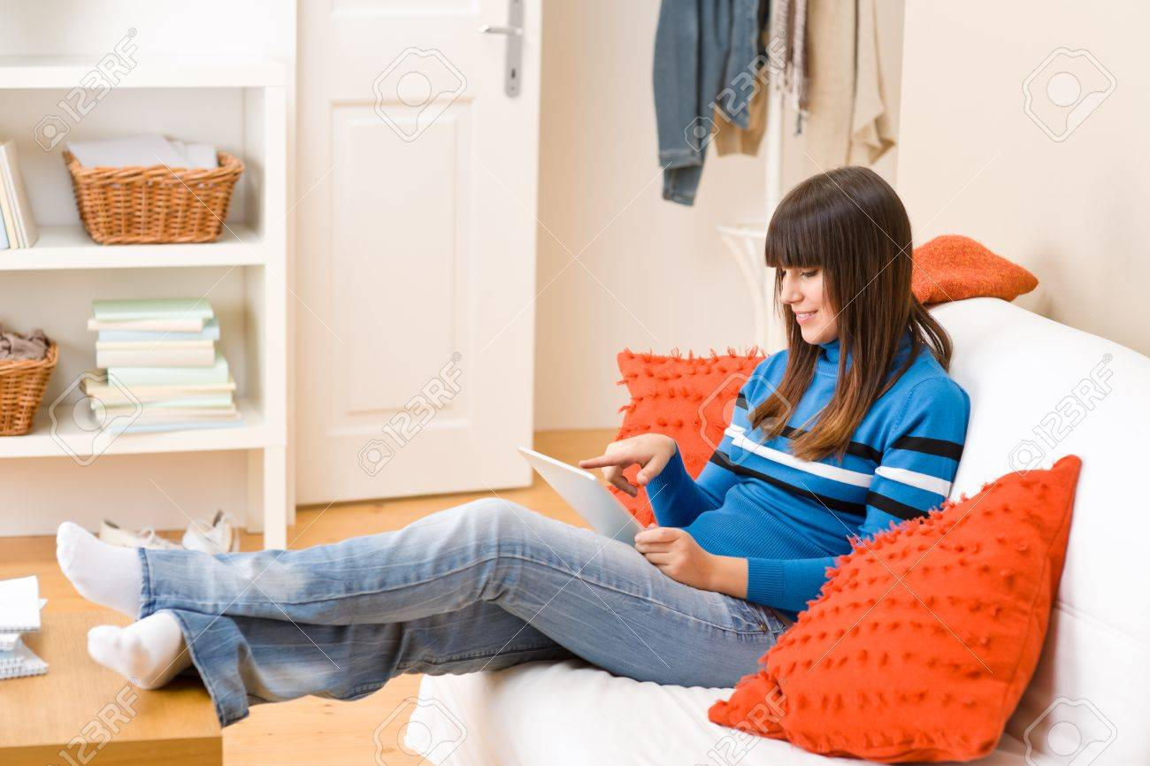 Teenager Girl Relax Home Sitting On Sofa With Touch Screen