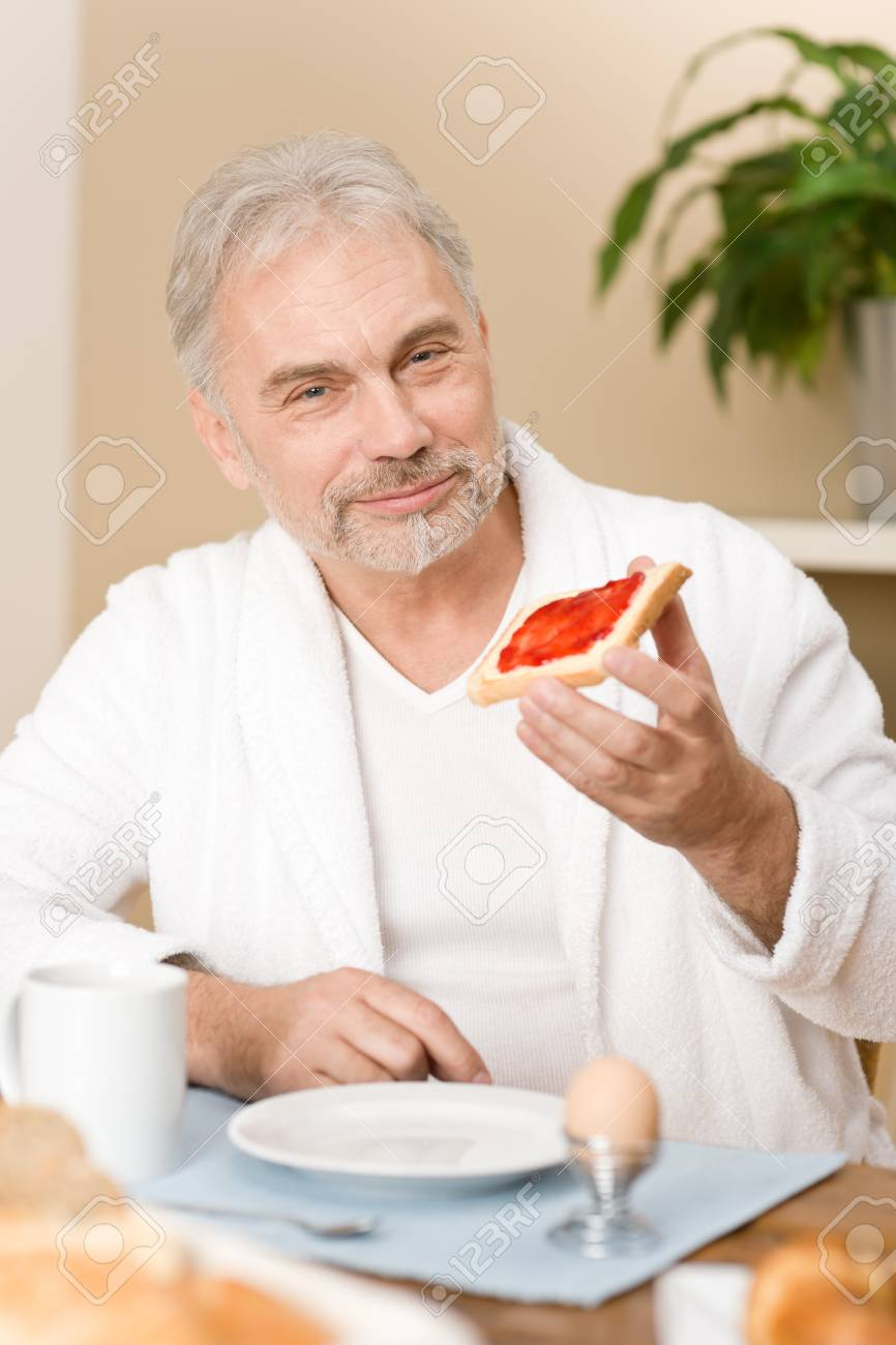 Senior mature man - breakfast at home with orange juice, coffee and egg Stock Photo - 8745741