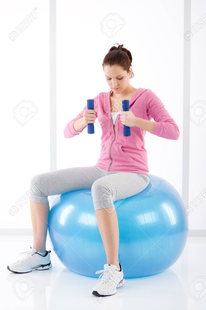 Fitness happy woman exercise dumbbell ball on white Stock Photo - 9318736