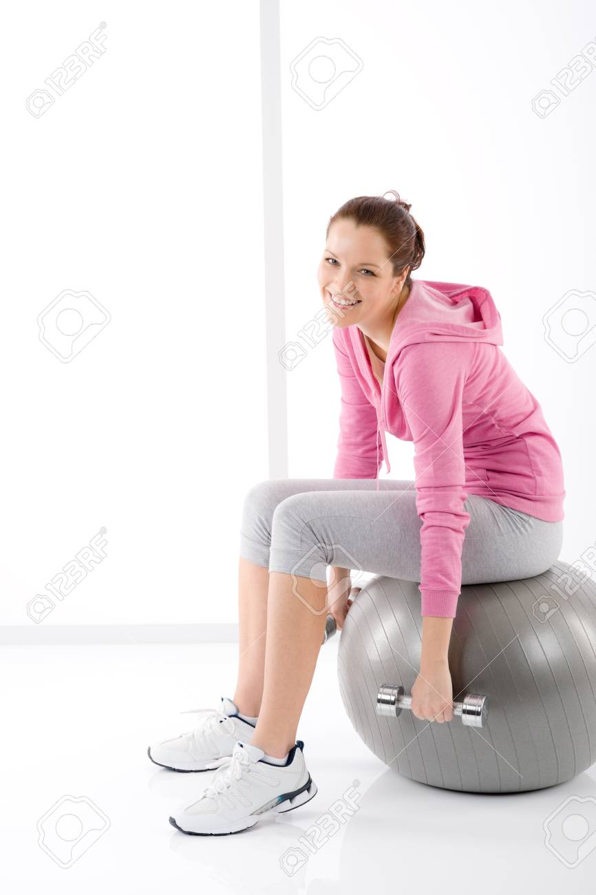 Fitness happy tired woman exercise dumbbell ball on white Stock Photo - 9331772