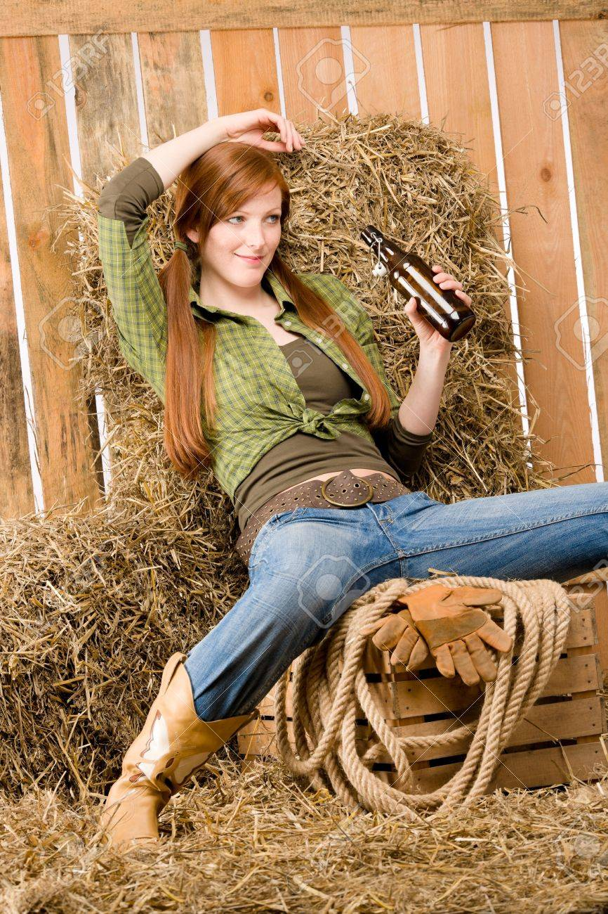 Provocative young cowgirl drink beer in barn country style Stock Photo - 9682673