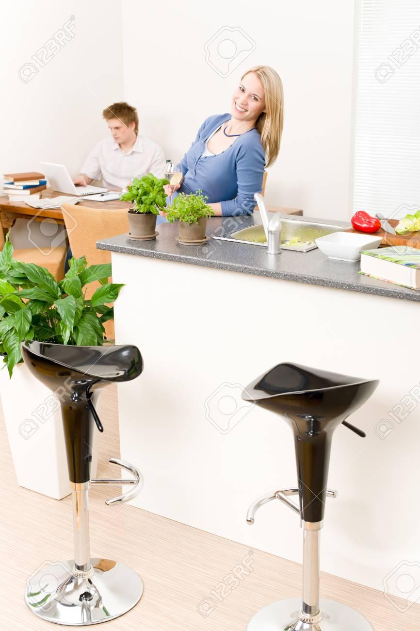 Happy woman cook enjoy white wine in kitchen, man in background Stock Photo - 9682310