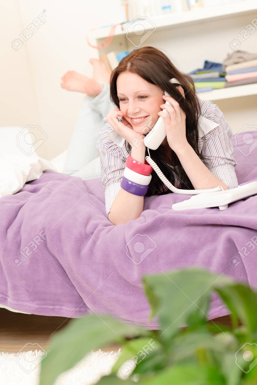 Student apartment - happy young girl on phone lying on bed Stock Photo - 9682354
