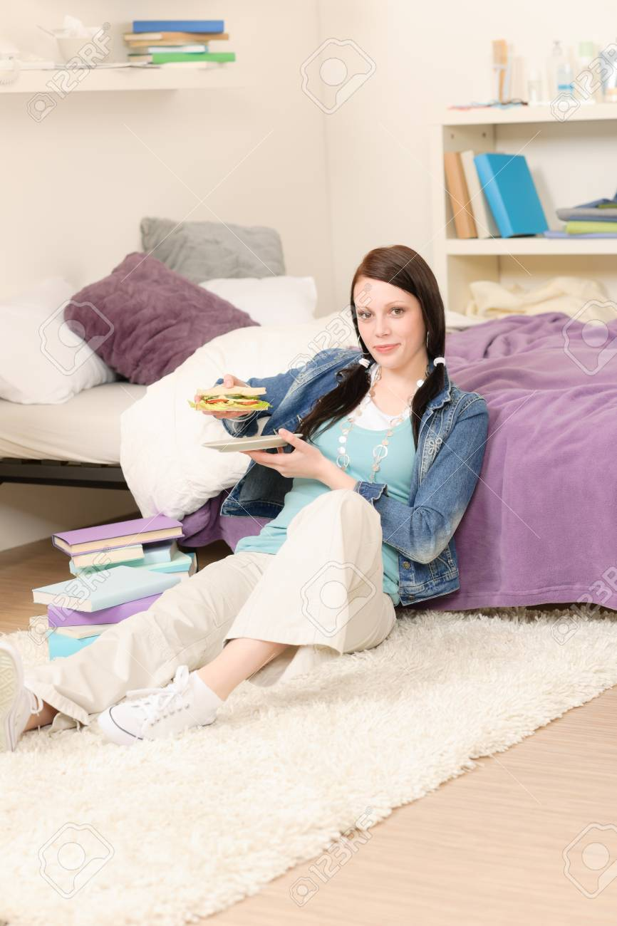 Young happy student have sandwich sitting in student apartment Stock Photo - 9682489