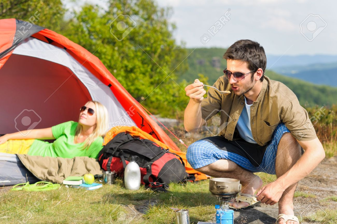 Happy camping couple with tent backpack cooking in sunny countryside - 10082489