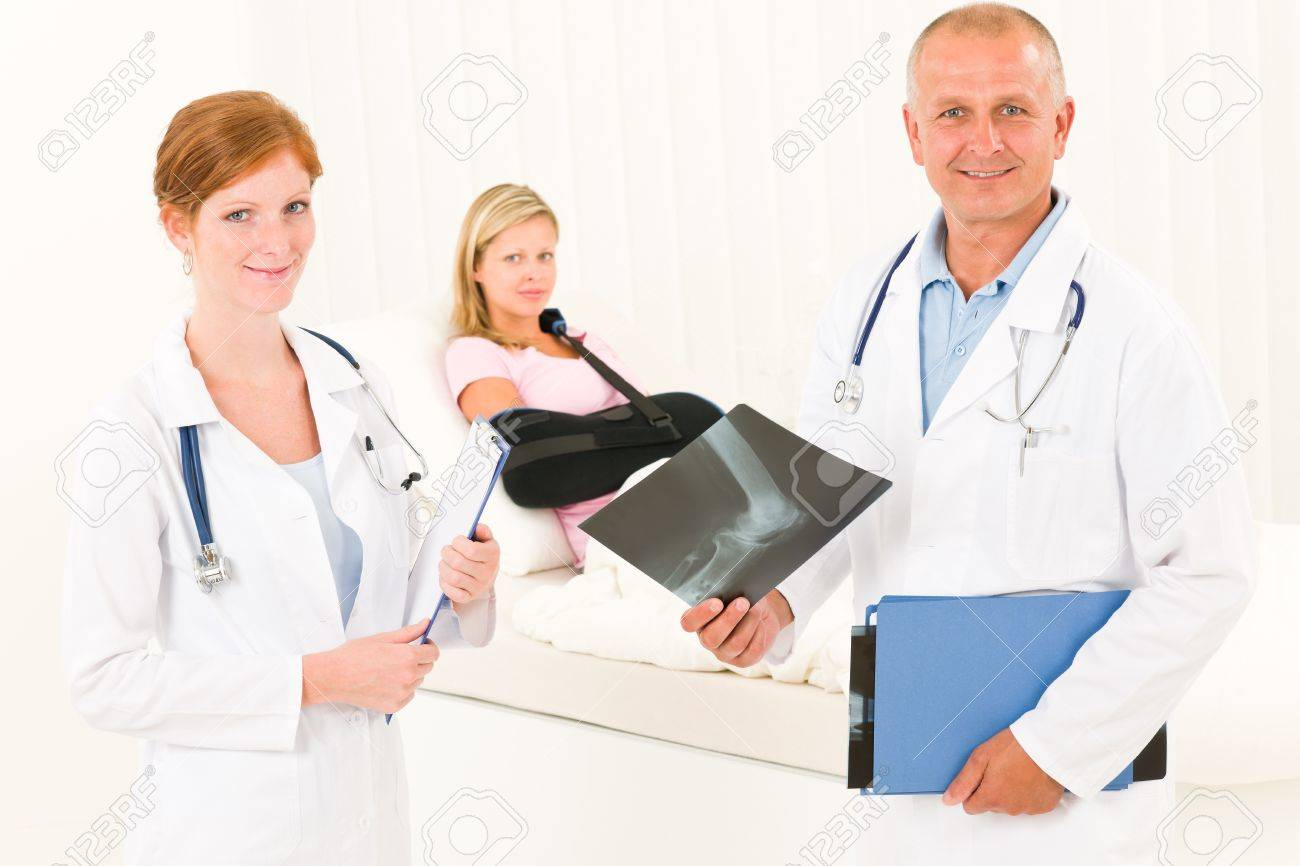 Medical doctors look at x-ray hospital patient in bed broken arm Stock Photo - 10223161
