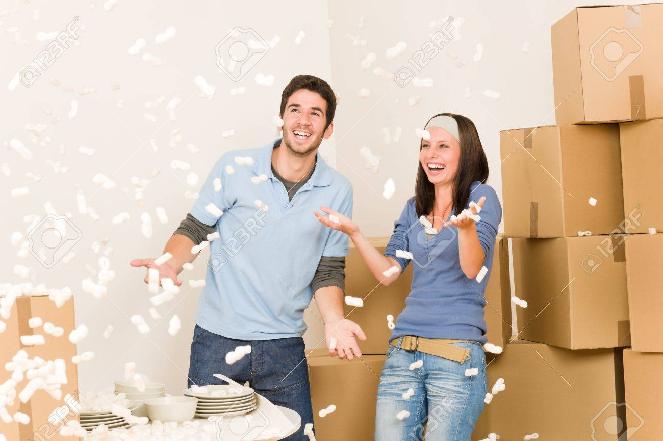 Moving home young cheerful couple throw foam peanuts unpacking boxes Stock Photo - 10449549