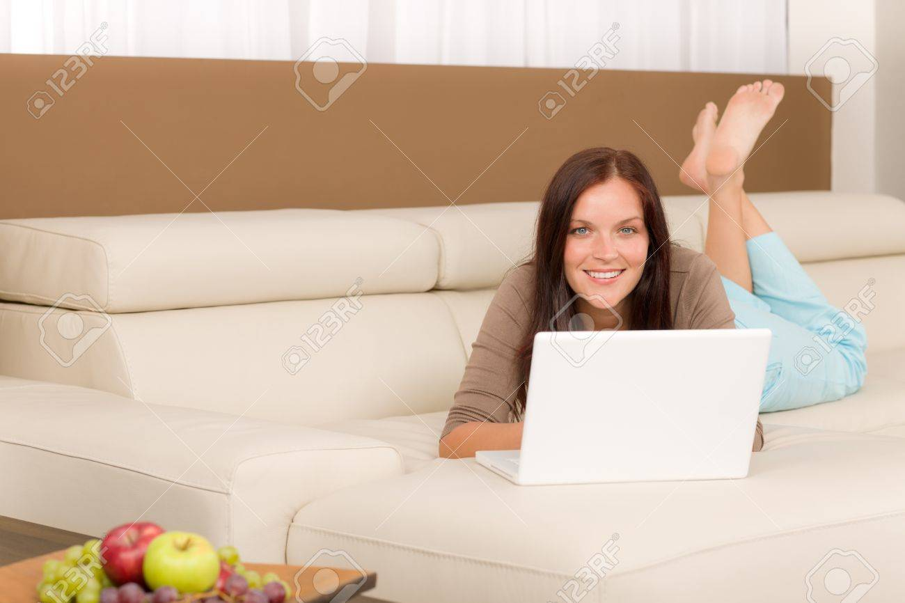 Attractive woman with laptop lying modern leather sofa living room Stock Photo - 10879649
