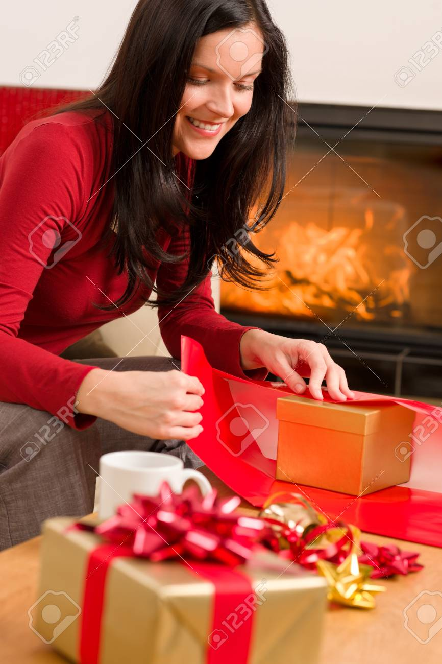 Happy woman in red wrapping christmas present by home fireplace Stock Photo - 11288013