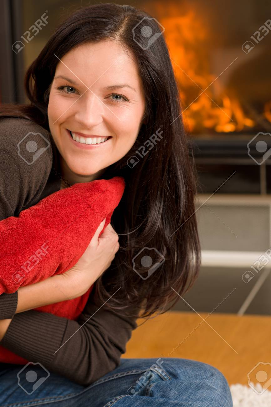 Beautiful happy young woman sitting front of home fireplace Stock Photo - 11476151