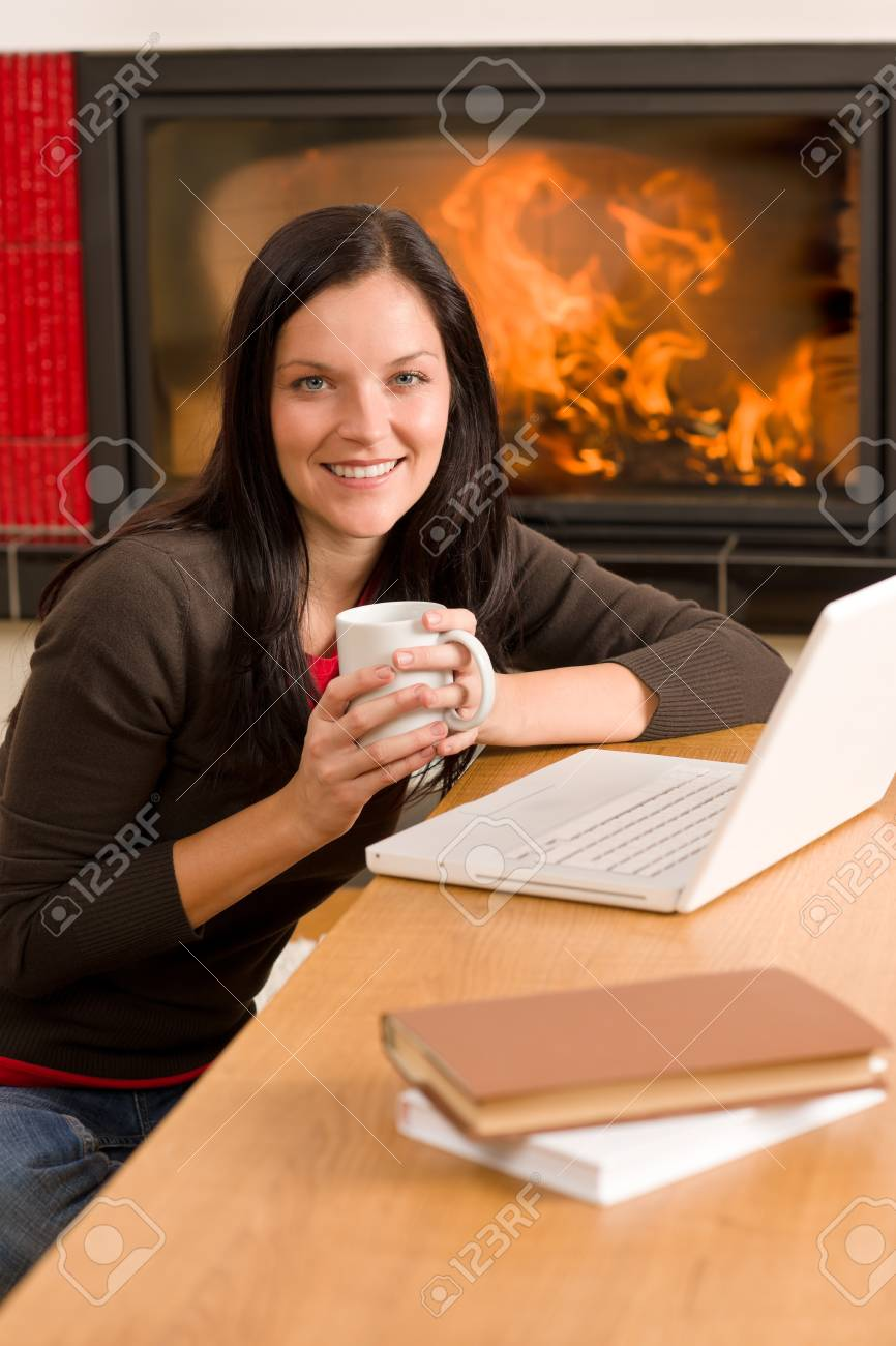 Happy woman at fireplace with laptop enjoying winter hot drink Stock Photo - 11476414