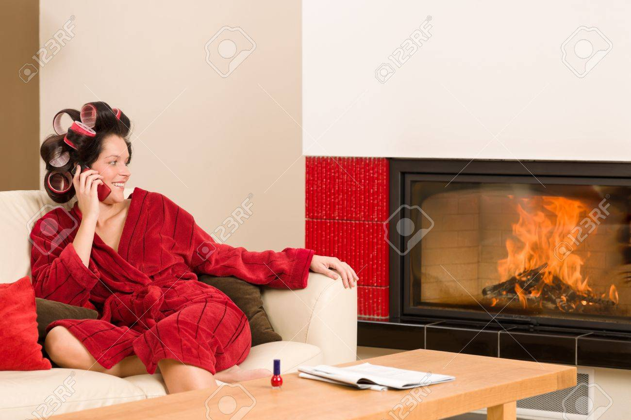 Home beauty woman with curlers calling phone fireplace red bathrobe Stock Photo - 11476348