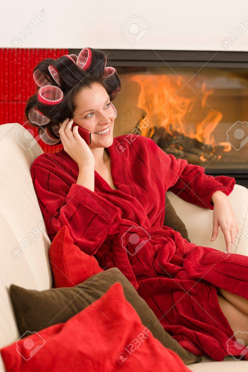 Home beauty woman with curlers calling phone fireplace red bathrobe Stock Photo - 11476116