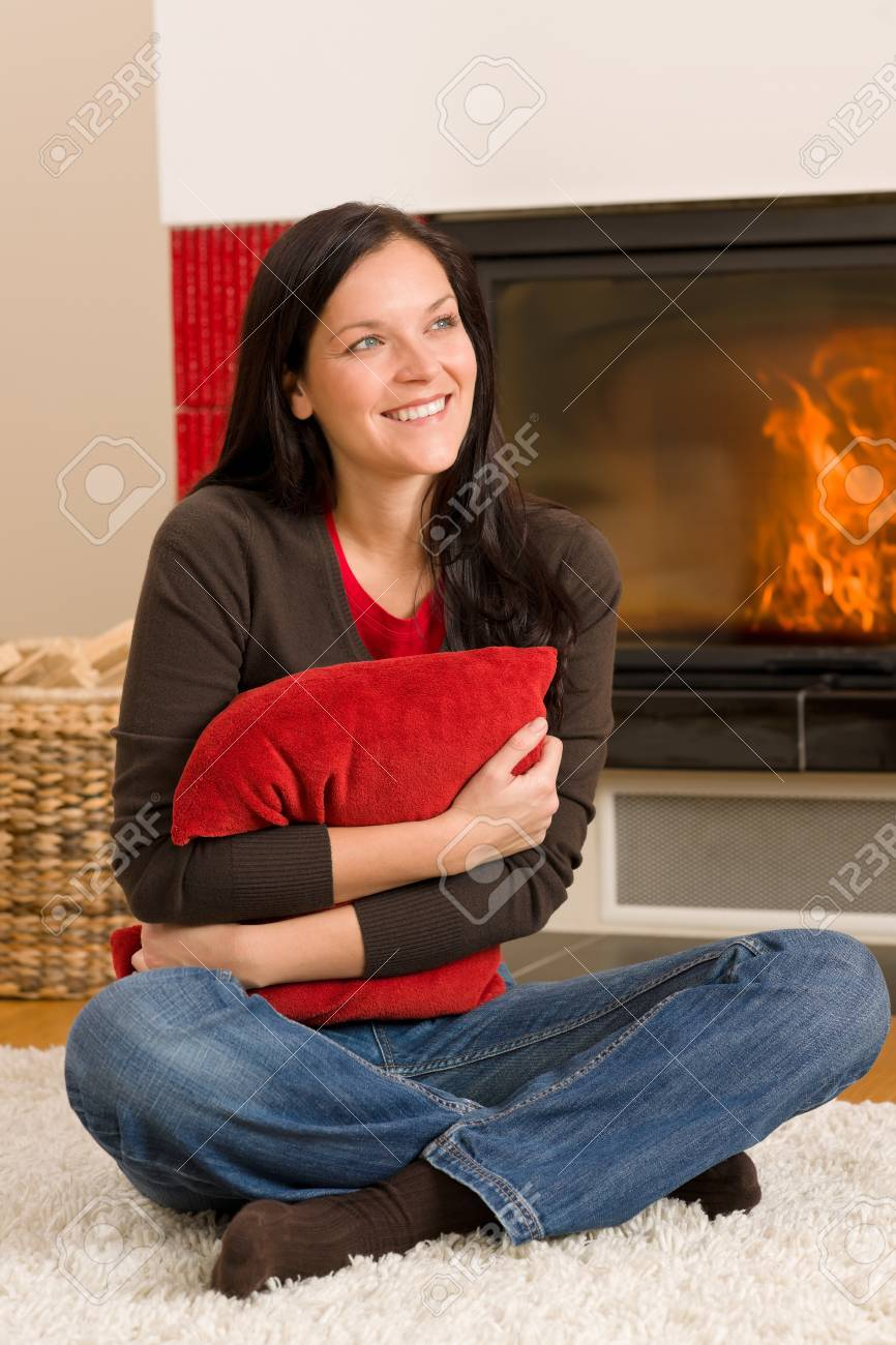 Beautiful happy young woman sitting front of home fireplace Stock Photo - 11476133