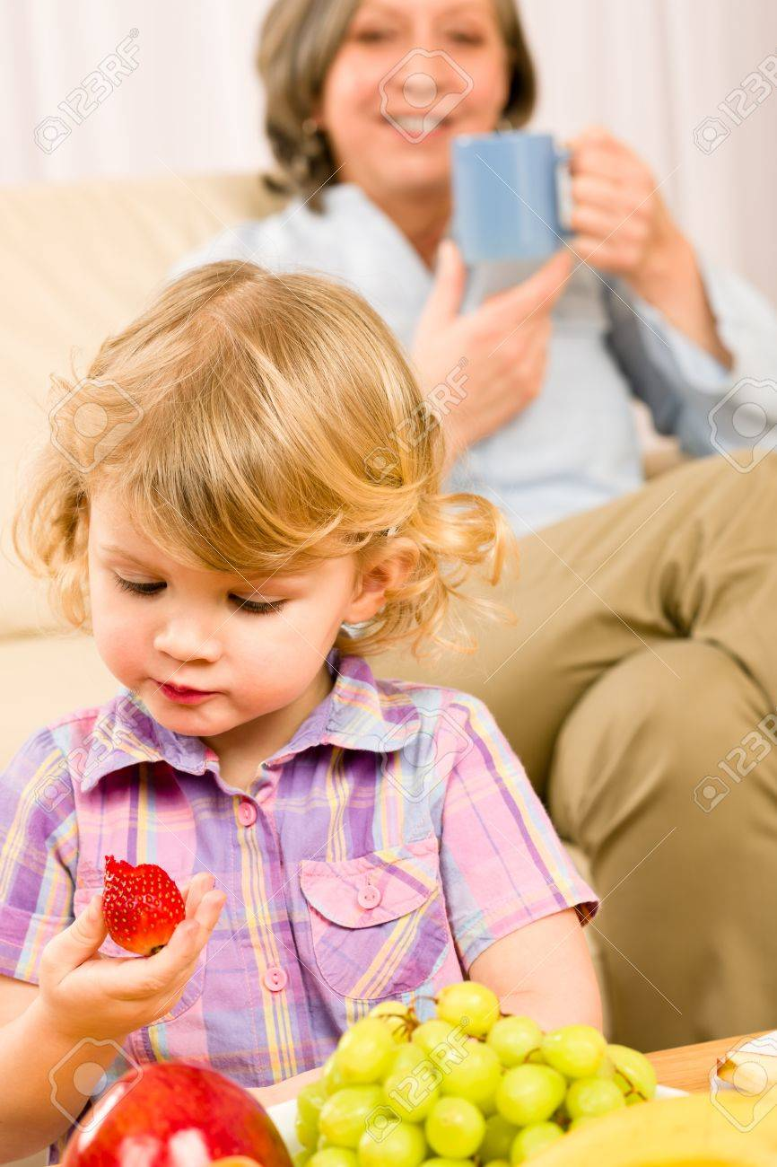 Little girl eat strawberry fruit with grandmother relaxing on sofa Stock Photo - 12079923