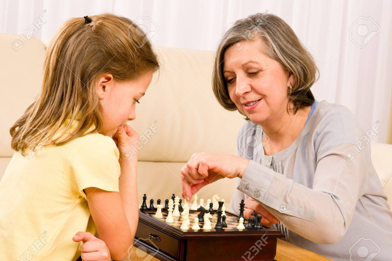 Grandmother and young girl playing chess together at home Stock Photo - 12079928