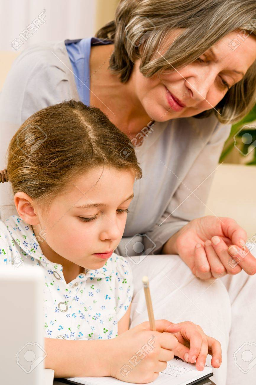 Grandmother help granddaughter doing school homework together at home Stock Photo - 12079925