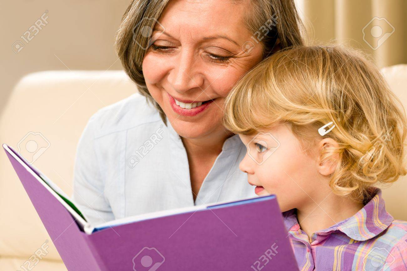 Grandmother and little girl reading book happy together at home Stock Photo - 12343544