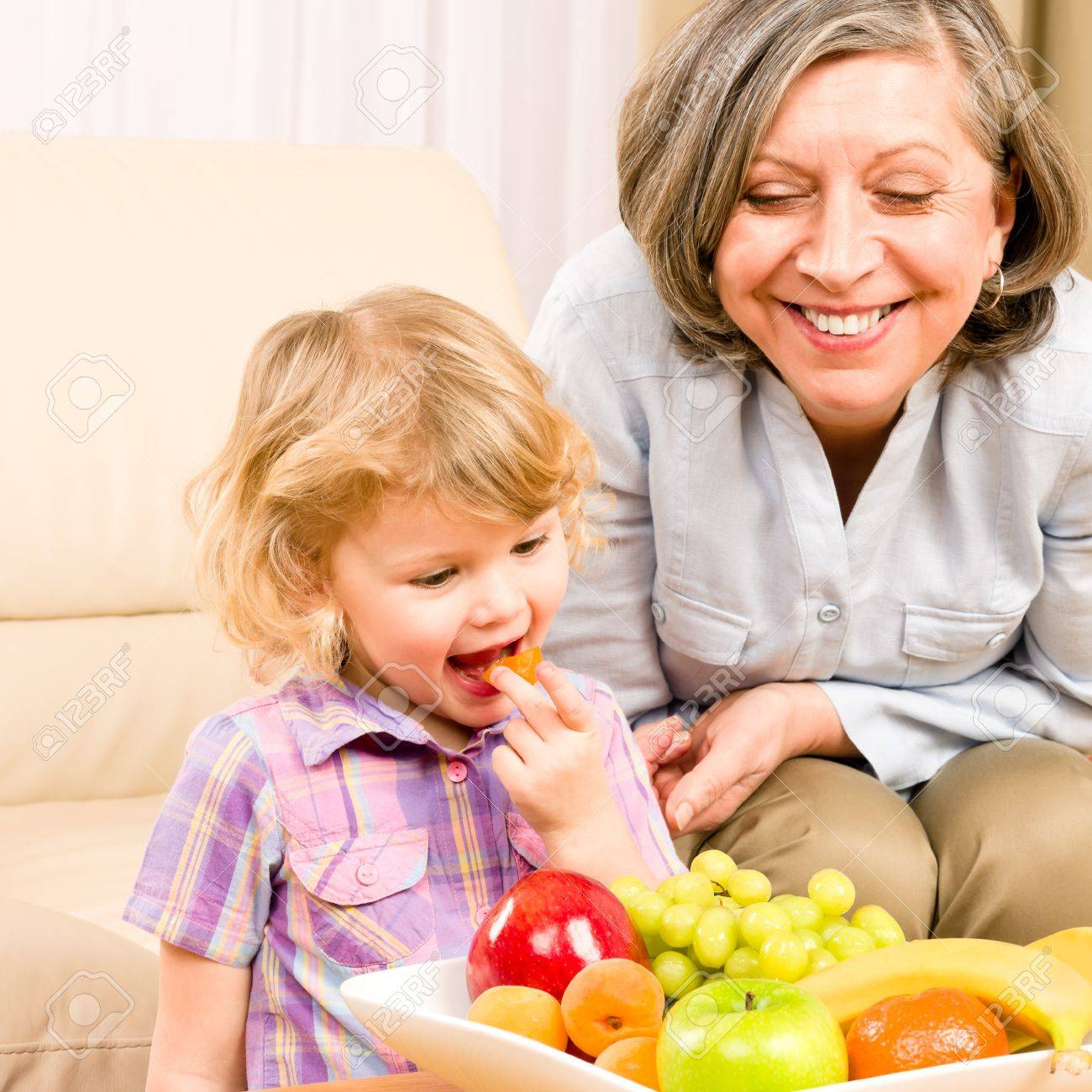 Little girl eat apricot fruit with grandmother relaxing on sofa Standard-Bild - 12343452
