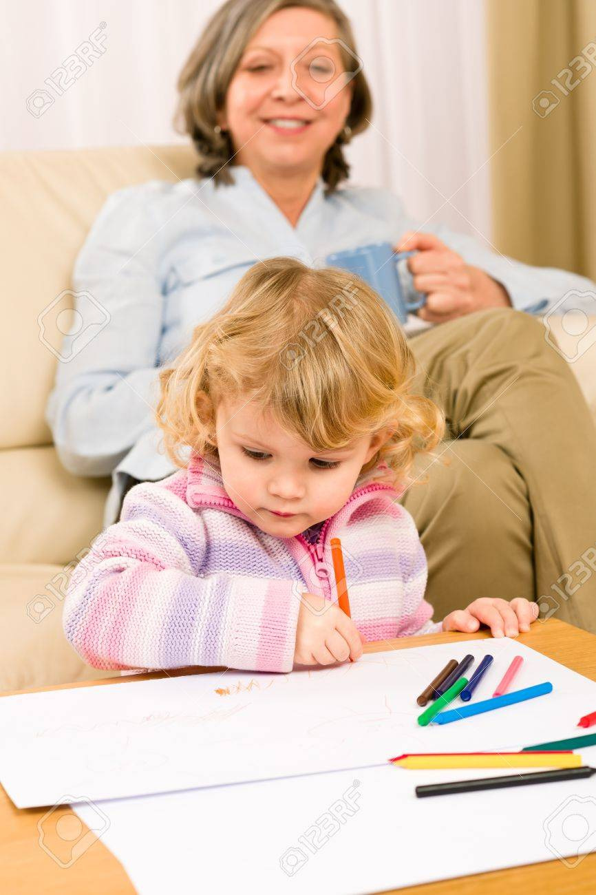 Grandmother and little girl drawing together with pencils at home Stock Photo - 12343550