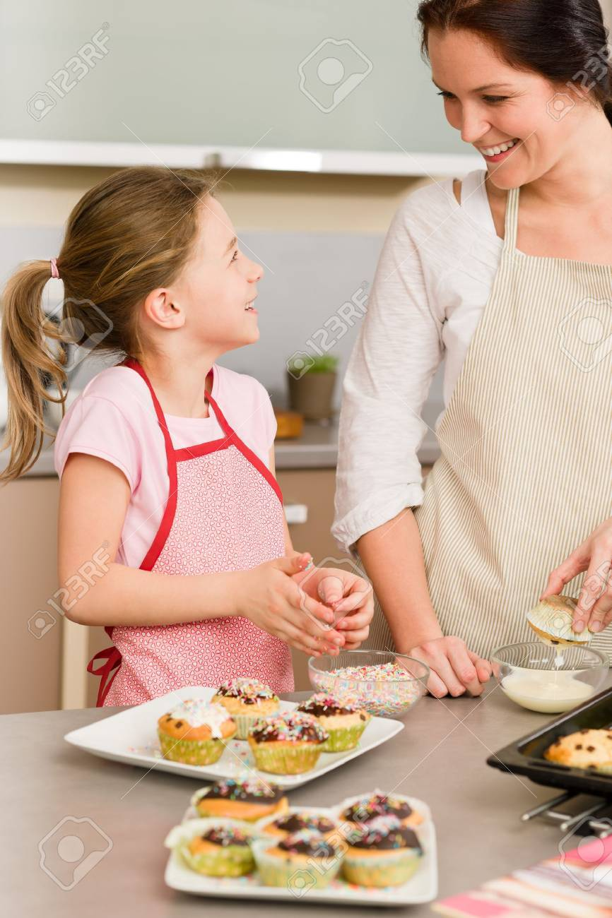 Mother and daughter decorating cupcakes sprinkles happy together at home Stock Photo - 12757891