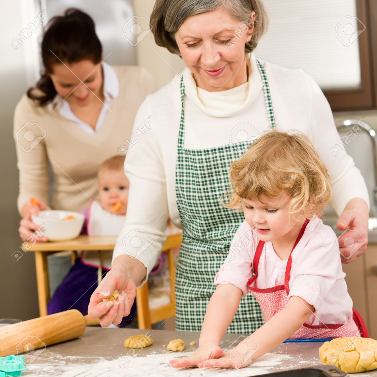 Grandmother with little girl prepare dough for baking in kitchen Stock Photo - 12757931