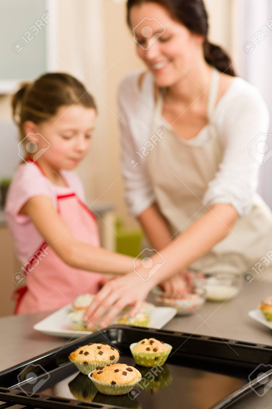 Cupcakes little girl decorate with sprinkles muffins with mother Stock Photo - 12758227