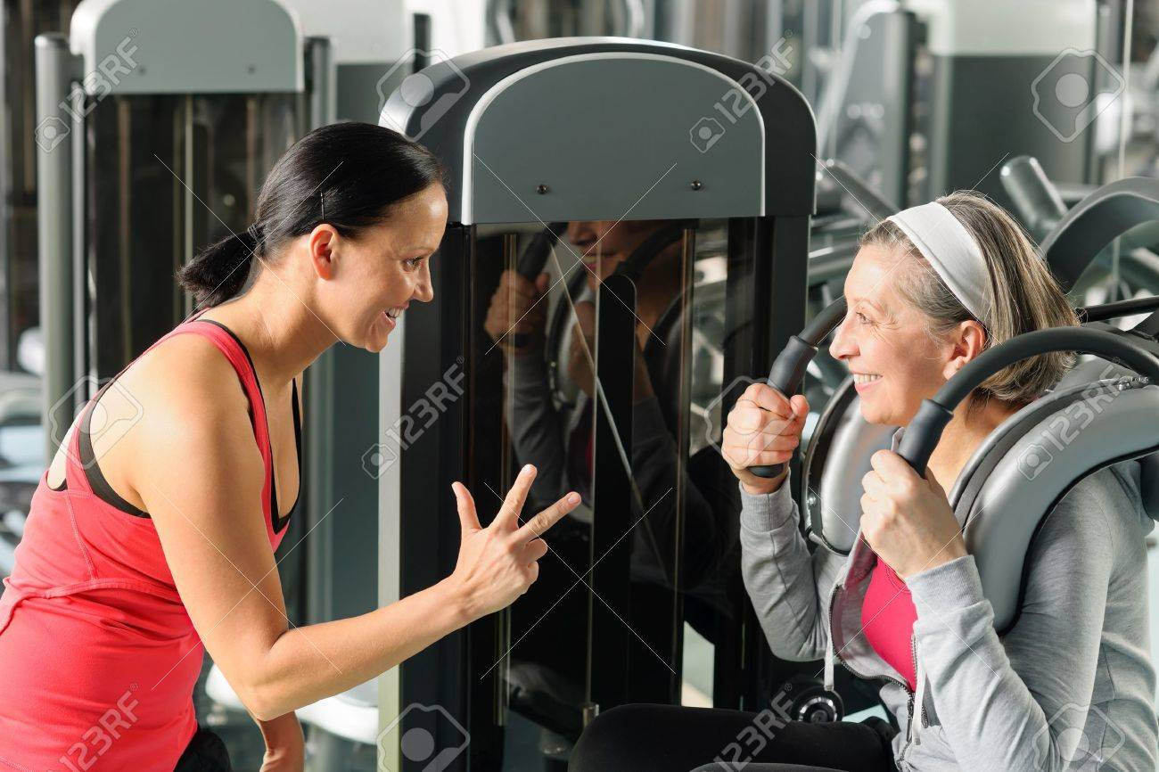 Fitness center senior woman exercise abdominal muscles with personal trainer Stock Photo - 12756845