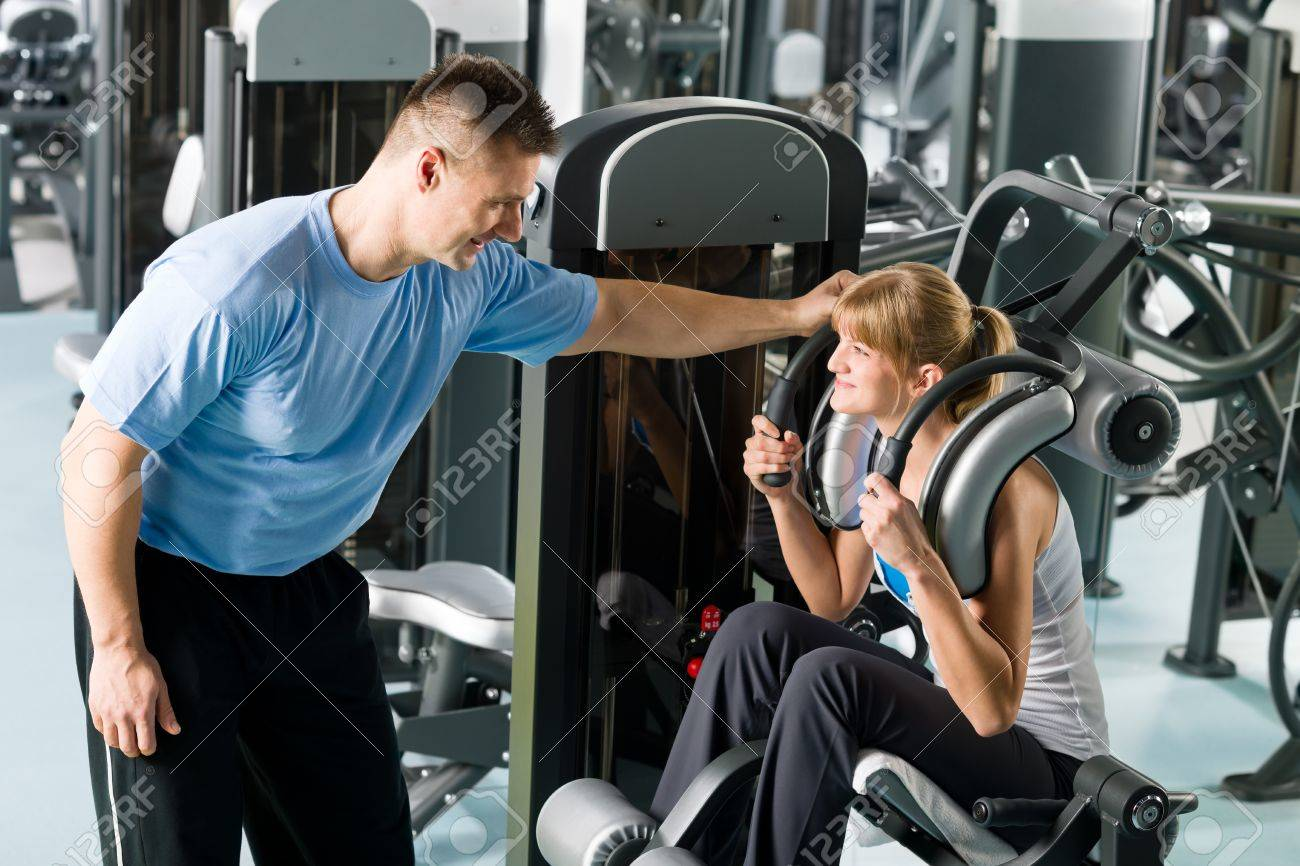 Fitness center young woman exercise with personal trainer on gym machine Stock Photo - 12758368