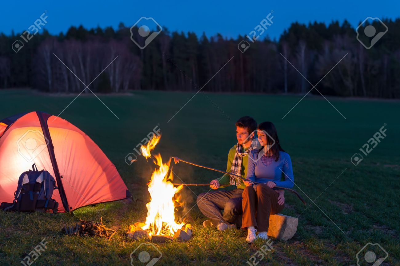 Camping night couple cook by campfire backpack in romantic countryside Stock Photo - 13125671