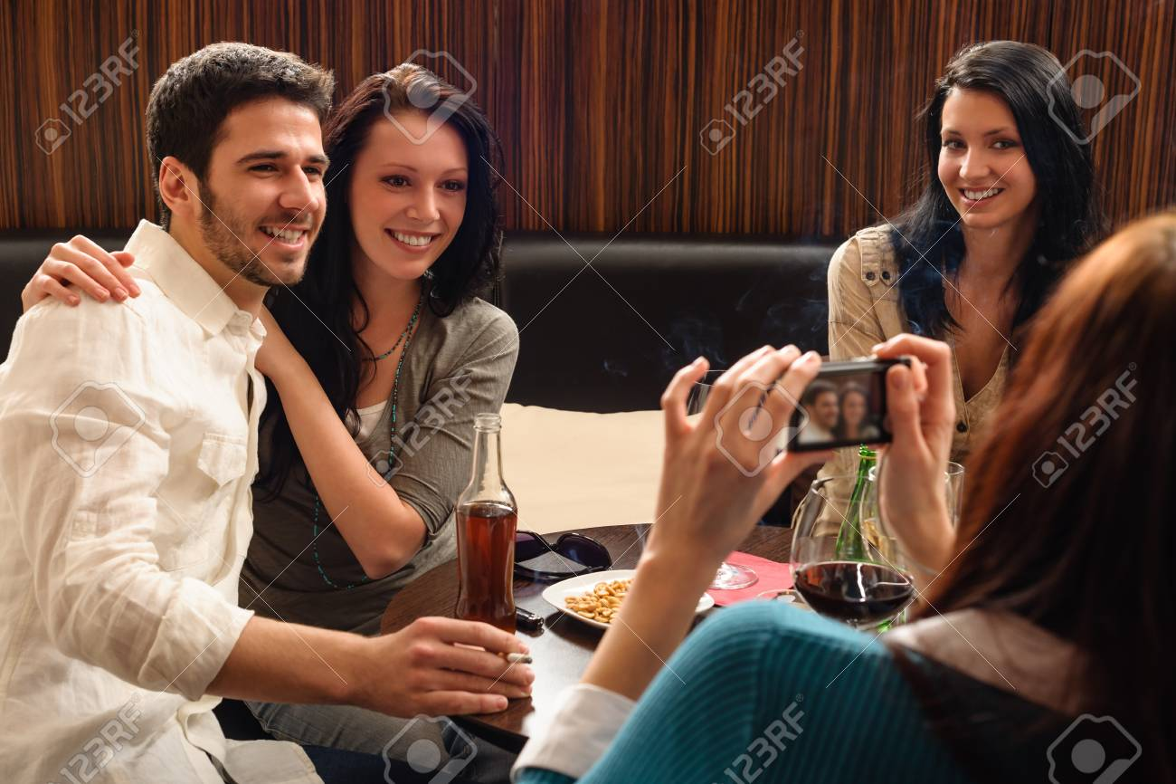 Young friends at the bar woman take picture of couple Stock Photo - 13258582