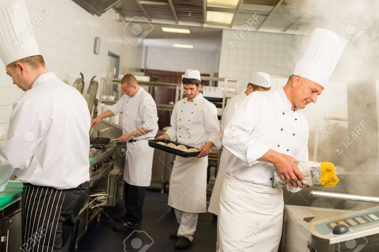 Professional kitchen busy team cooks and chef prepare meal Standard-Bild - 30203767