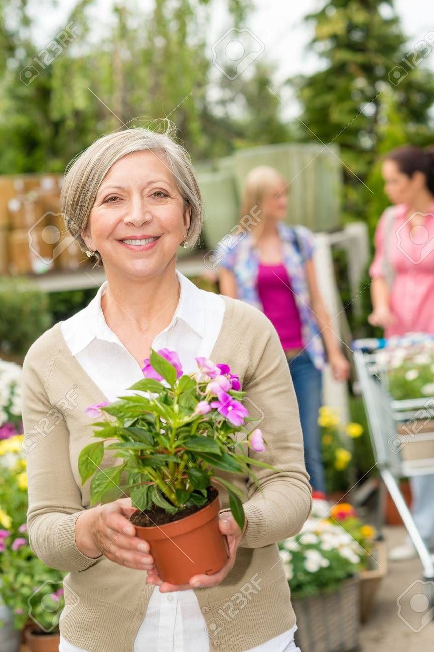 Senior lady shopping for flowers at garden centre smiling Stock Photo - 14181847