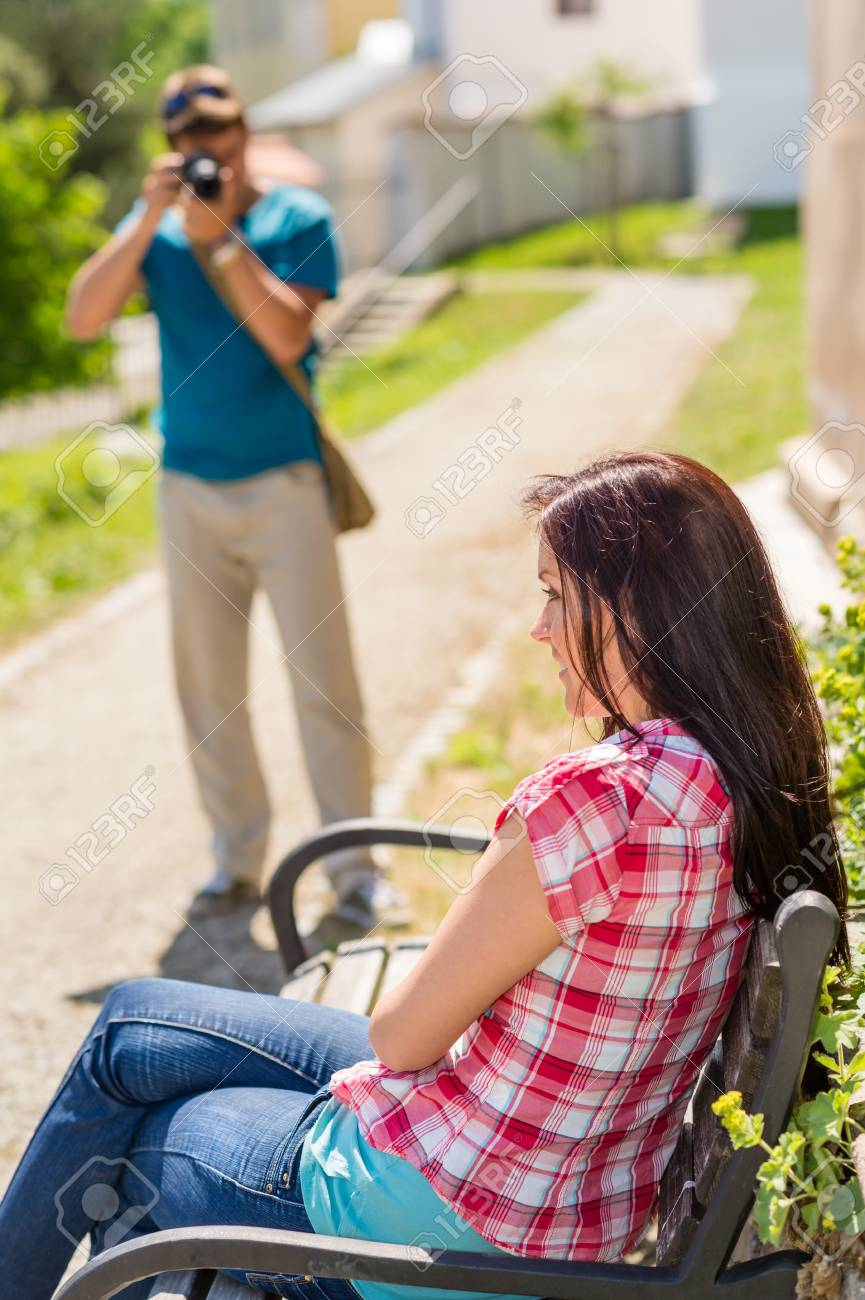 Young man take photo of his girlfriend sitting park bench Stock Photo - 14242190