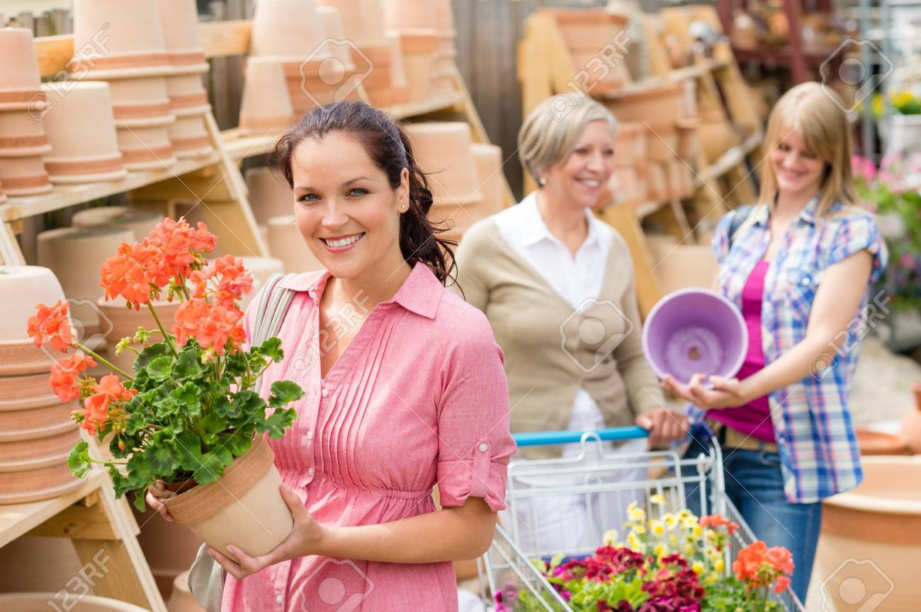 Young woman holding geranium in clay pot at garden centre Stock Photo - 14449947