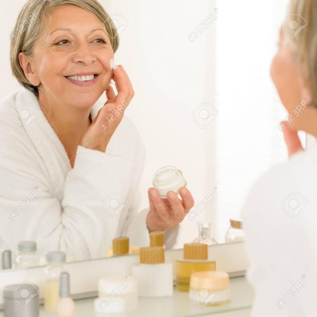 Smiling senior woman apply anti-wrinkles cream looking in bathroom mirror Stock Photo - 14605257