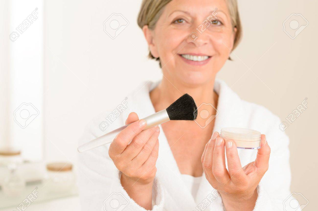 Mature woman hold brush and make up powder in the bathroom stock