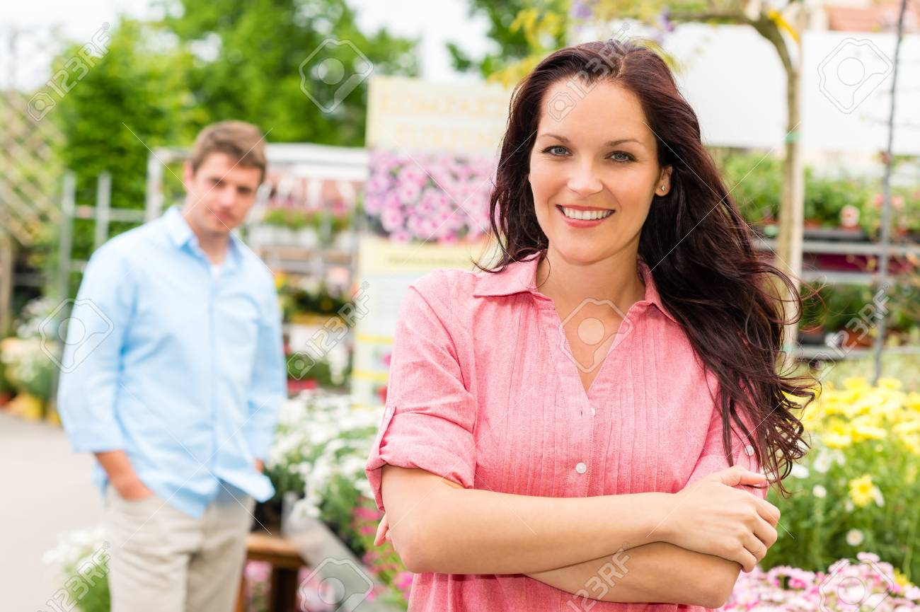 Smiling woman posing at garden centre young man in background Stock Photo - 14639903