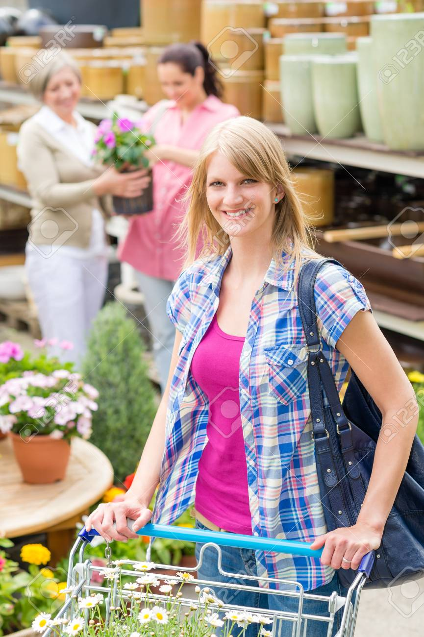 Young woman with trolley shopping for flowers at garden centre Stock Photo - 14823846