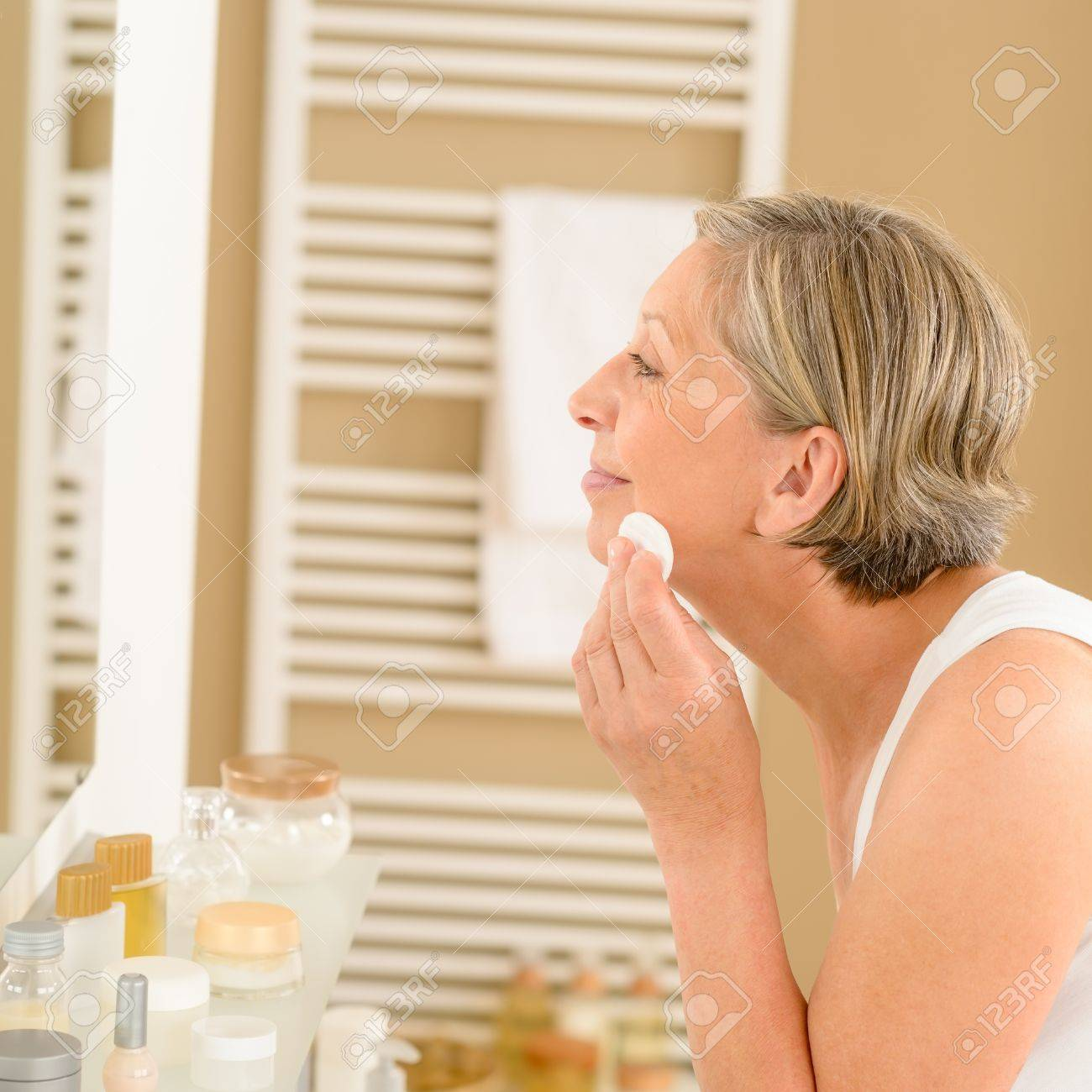 Senior woman clean face with cotton pad  looking bathroom mirror Stock Photo - 14899962