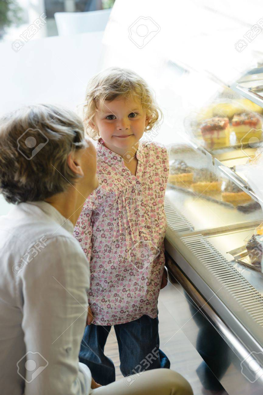 Woman with child girl in bakery choose cake grandmother and granddaughter Stock Photo - 15099347