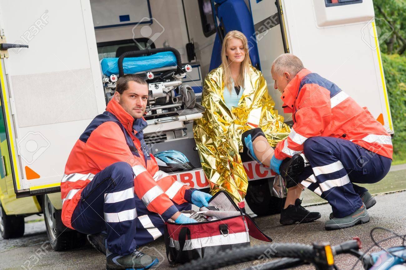 Bike accident woman emergency doctor checking leg in ambulance - 15412680