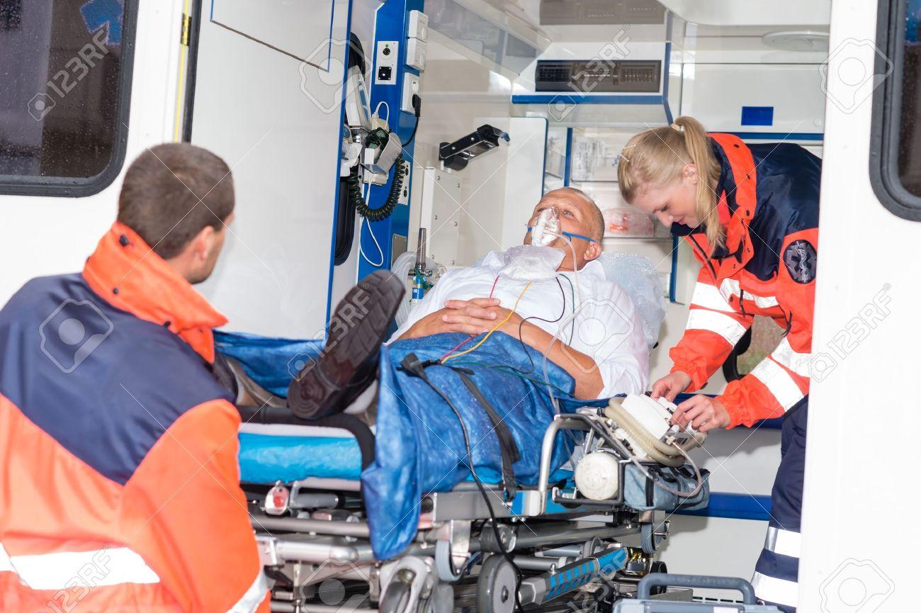 Paramedics putting patient man oxygen mask in ambulance car - 15412675
