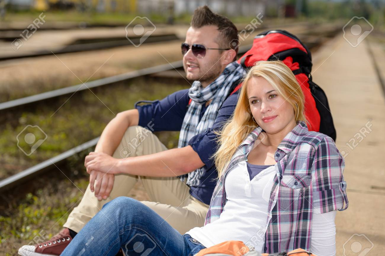 Couple backpack traveling resting on railroad trip tourists vacation togetherness Stock Photo - 16968377