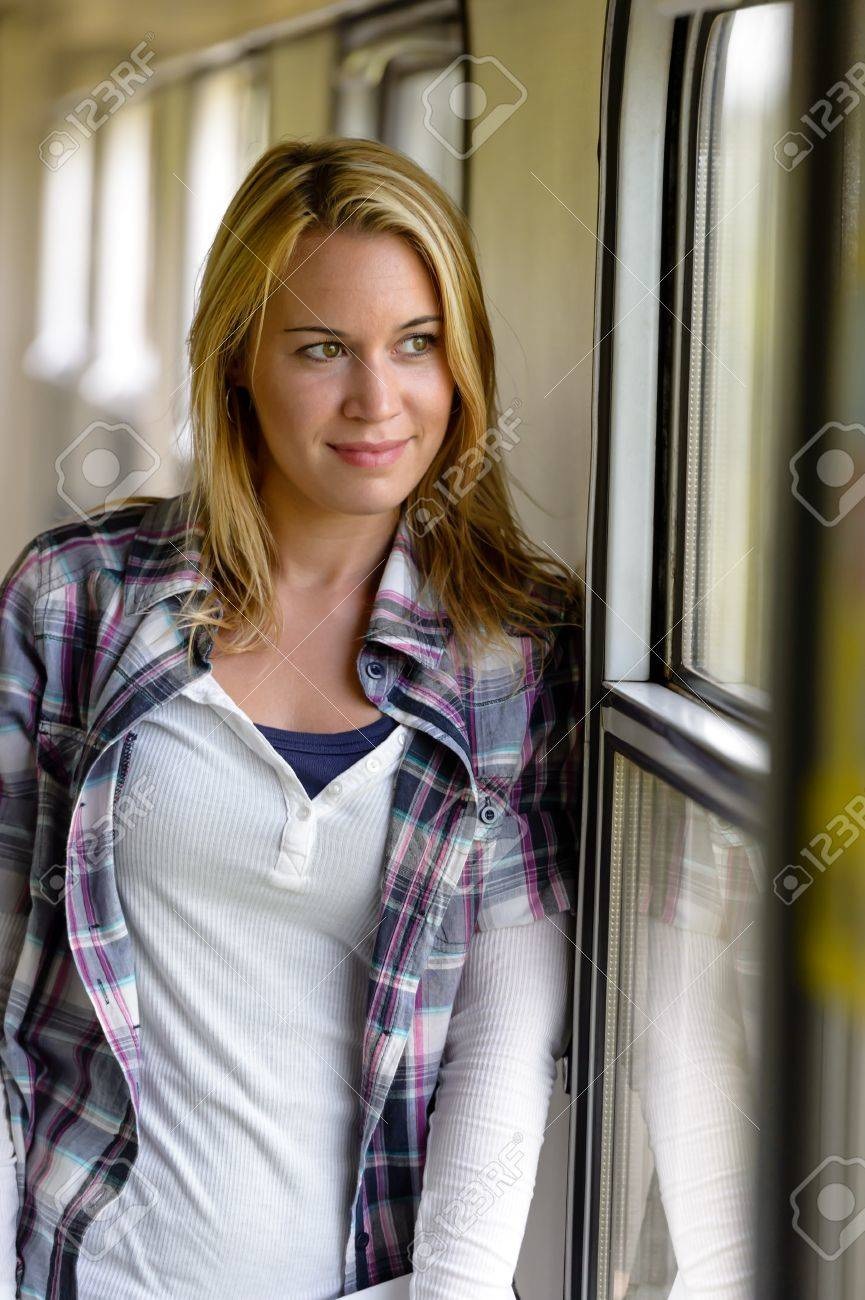 Woman looking out the train window smiling vacation traveling pensive Stock Photo - 16968384