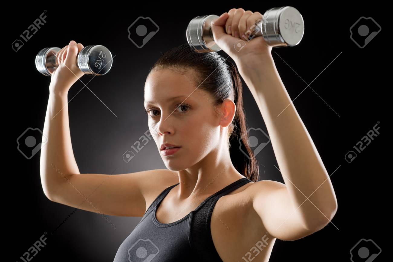 Portrait of sporty young woman holding dumbbells on black background Stock Photo - 16985383